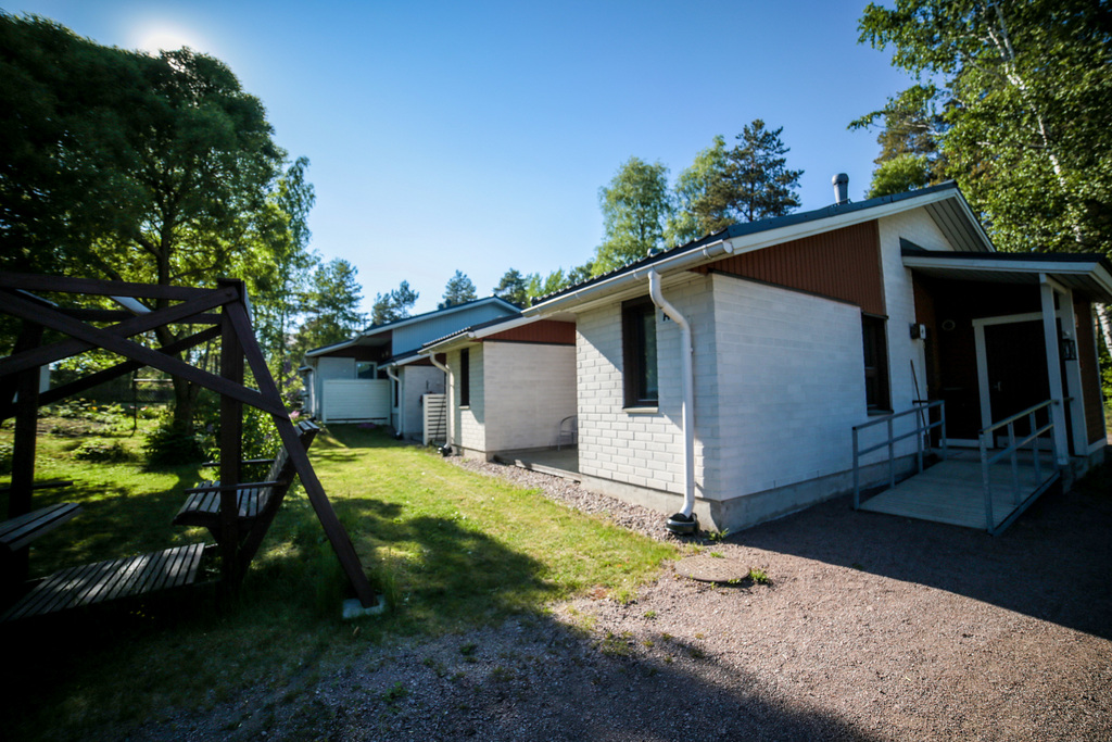 Rivitalon pihalla paistaa aurinko. Pihakeinu on varjossa. Haminan Ravimäki tarjoaa kaupunkilaisille myös työpalvelua, esimerkiksi pihanhoitoa.
