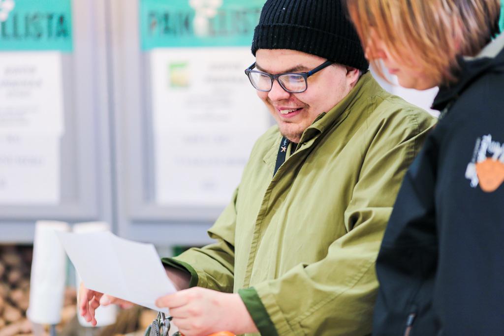 Asukas lukee kauppalistaa ohjaajan kanssa ja nauraa. Tukiasuminen Haminan Ravimäessä sopii aikuisille, jotka pystyvät itsenäisempään elämään.