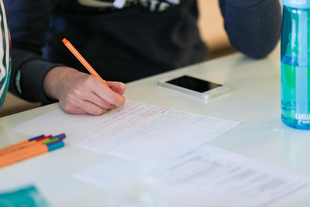Asukas kirjoittaa paperille. Pöydällä on värikkäitä kyniä, puhelin ja vesipullo. Ravimäki järjestää asukkailleen kerhoja ja toimintaa.