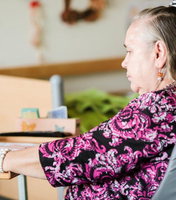 Nainen värittää kuvaa pöydän ääressä, hoitajan käsi olkapäällä. Asukas arvostaa oman kodin rauhaa yksiössä Haminan Ravimäessä.